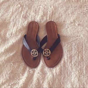Tan, black, and gold flip flop sandals